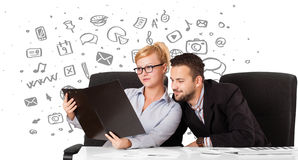 Businessman and businesswoman with all kind of hand-drawn icons Royalty Free Stock Image