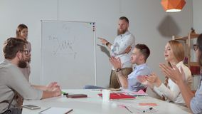 Quarrel during business presentation. Businessman and businesswoman arguing by the white board with graphs and charts during business presentation on a meeting stock footage