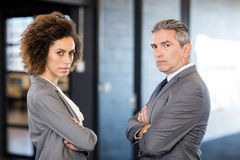 Businessman and businesswoman with arms crossed Stock Photos