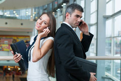 Businessman and Businesswoman back to back on mobile phones Stock Photography