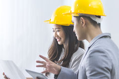 Businessman and businesswoman with blueprint and helmets discuss Stock Image