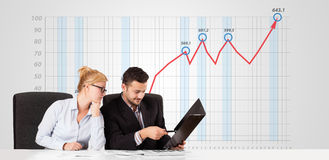 Businessman and businesswoman calculating stock market with risi Stock Photography