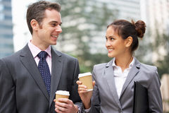 Businessman And Businesswoman Chatting In Street. Holding Takeaway Coffee stock photography