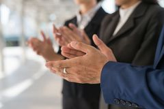 Businessman and businesswoman clap their hands to congratulate the signing of contract between their companies. Success, greeting and partner concept royalty free stock image
