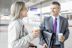 Businessman and businesswoman with coffee cups talking at railroad platform Royalty Free Stock Images