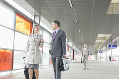 Businessman and businesswoman conversing while walking in railroad station Stock Image