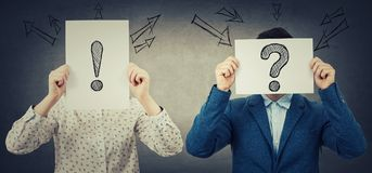 Hiden face expressions. Businessman and businesswoman covering their faces using white paper sheets with drawn interrogation and exclamation marks, like a mask Royalty Free Stock Images