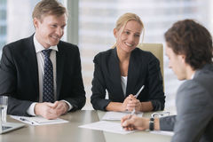 Businessman and businesswoman deceiving a client. Businessman and businesswoman with tricky sweet smiles, a men unaware of bad intentions, signing a contract or Stock Image