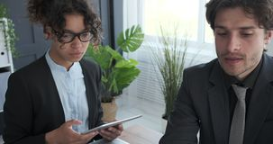 Business colleagues working at office. Businessman and businesswoman with digital tablet at office meeting stock video footage