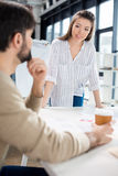 Businessman and businesswoman discussing and brainstorming at workplace in small business office. Young businessman and businesswoman discussing and Royalty Free Stock Photos