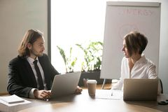 Businessman and businesswoman discussing business ideas in board. Focused serious business people in formal wear talking at meeting in boardroom, two business Royalty Free Stock Photos