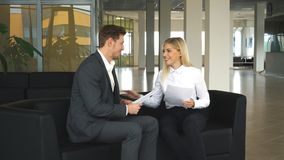Businessman and businesswoman discussing business plans in the lobby of the office on the couch. Business meeting in modern office two business people stock footage