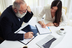 Businessman and businesswoman discussing documents and ideas Royalty Free Stock Image