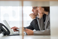 Businessman and Businesswoman Discussing While Looking at Laptop Royalty Free Stock Image