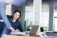 Businessman and businesswoman discussing over documents at desk in office Royalty Free Stock Image