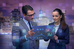 The businessman and businesswoman discussing trading strategies. Businessman and businesswoman discussing trading strategies Stock Photo