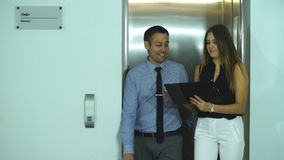 Businessman and businesswoman emerging from Elevator and discuss business ideas. In office stock video footage