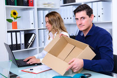 Businessman and businesswoman with empty delivery box in the off Stock Image