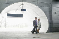 Businessman and businesswoman entering railroad station Stock Photo