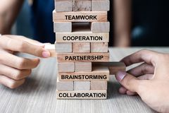 Businessman and Businesswoman hand placing or pulling wooden block on the tower building. Business, Teamwork, Brainstorming, stock photography