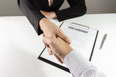 Businessman and businesswoman handshake over loan agreement docu Stock Image