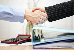 Businessman and businesswoman are handshaking over binders Royalty Free Stock Photo