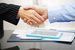 Businessman and businesswoman are handshaking over documents and Stock Photo