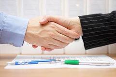 Businessman and businesswoman are handshaking over signed contra Stock Image