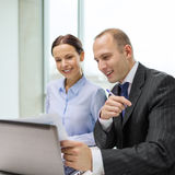 Businessman and businesswoman having discussion. Business, technology and office concept - businessman and businesswoman with laptop computer and papers having Stock Photo