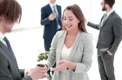Businessman and businesswoman holding a pot with sprouts. The concept of eco-business stock photos