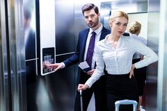 businessman and businesswoman in hotel elevator looking stock photography