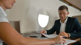 Businessman and businesswoman inside of modern luxury private jet signing big business agreement stock video