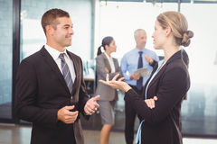Businessman and businesswoman interacting with each other. In office stock images