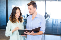 Businessman and businesswoman interacting holding organizer Stock Photos