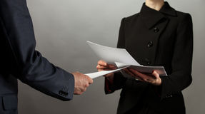 Businessman and businesswoman interchange of documents Royalty Free Stock Photos