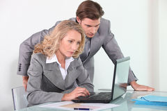 Businessman and businesswoman with laptop computer Stock Images