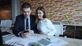 Businessman and businesswoman look at the mobile phone. stock video footage