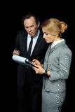 Businessman and businesswoman looking at clipboard with papers on black Royalty Free Stock Photos