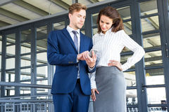 Businessman and businesswoman looking at smartphone Royalty Free Stock Image