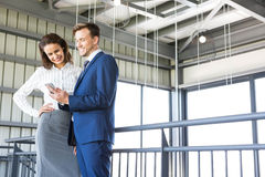 Businessman and businesswoman looking at smartphone Stock Images