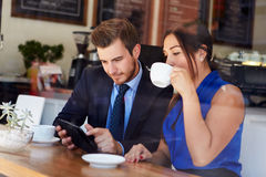 Businessman And Businesswoman Meeting In Coffee Shop. Using Digital Tablet Drinking Coffee Royalty Free Stock Photography