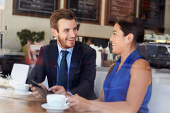Businessman And Businesswoman Meeting In Coffee Shop. Using Digital Tablet Smiling At Each Other Stock Photography