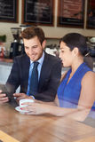 Businessman And Businesswoman Meeting In Coffee Shop. Wearing Smart Clothes Using Digital Tablet Royalty Free Stock Image