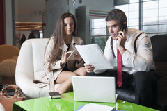Businessman and businesswoman at meeting with laptop and tablet Stock Images