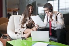 Businessman and businesswoman at meeting with laptop and tablet Royalty Free Stock Photo