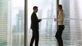 Businessman and businesswoman meeting in office standing by full-length window stock footage