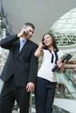 Businessman and businesswoman on mobile phones Stock Photos