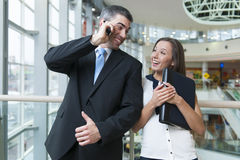 Businessman and businesswoman on mobile phones Stock Images