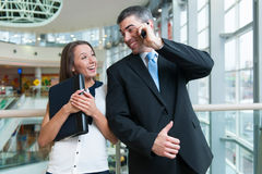 Businessman and businesswoman on mobile phones Stock Photo