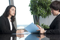 Businessman and businesswoman negotiating. In a stylish office with harbour in the background Stock Images